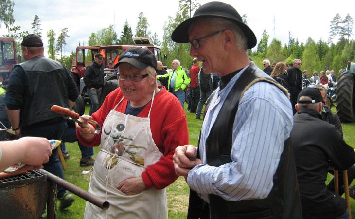 Gårdsägare Ulf Andersson tar gladeligen emot en korv från grillmästare Eva Peterson och Pia Jacobsson som inte syns på bilden.
